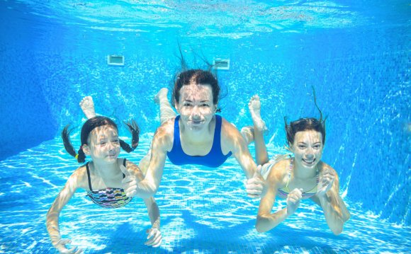 Family swim in pool underwater